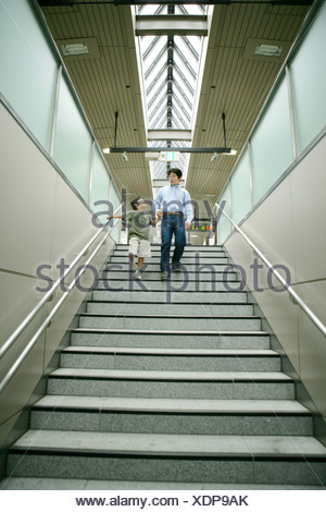 Low angle view of a young man and his son walking down stairs - Stock Photo