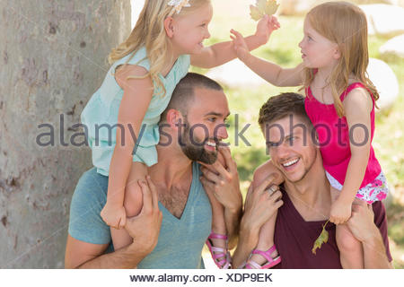 Two sisters sitting on fathers shoulders in park - Stock Photo