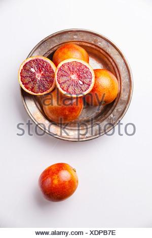 Ripe red oranges on white textured background - Stock Photo