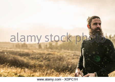 A man standing in sunlit open country in winter. - Stock Photo