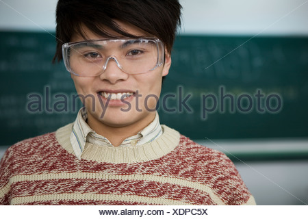 Male student wearing safety goggles - Stock Photo