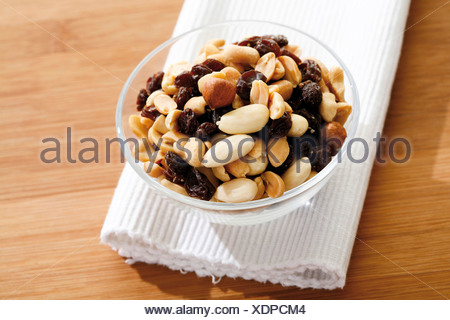 Trail mix, various nuts with raisins, in a glass bowl - Stock Photo