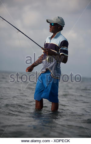 a fisherman holds fly fline while wading in shallow water - Stock Photo