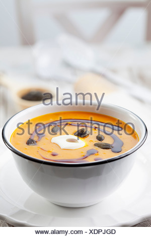 Pumpkin soup in old bowl garnished with pumpkin seed oil, pumpkin seeds and sour cream, studio shot - Stock Photo