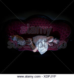 Canada, British Columbia, Greater Vancouver Regional District, Vancouver, Girl (8-9) and cat lying on sofa - Stock Photo