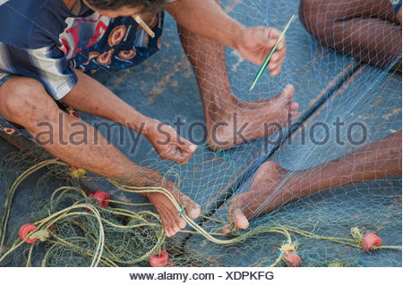 Men Making A Fishing Net To Get Ready To Catch Some Fish; Prachuap Thailand - Stock Photo