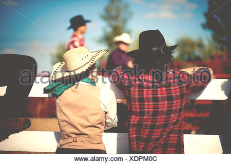 USA, Rear view of cowboy and cowgirl leaning on cattle fence, - Stock Photo