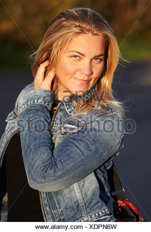 Portrait of a beautiful young blond woman in denim jacket smiling - Stock Photo