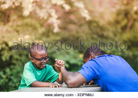 Father arm wrestling with son at parkland eco camp - Stock Photo