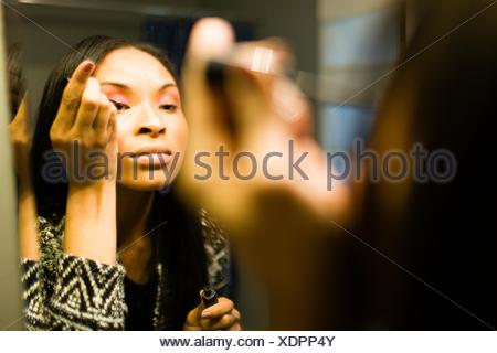 Over shoulder mirror image of young woman putting on eye shadow in bathroom - Stock Photo