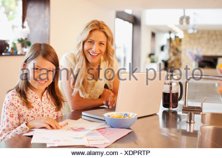 Mother and daughter relaxing in kitchen - Stock Photo