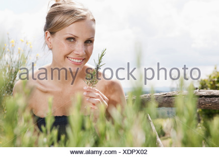 Italy, Tuscany, Magliano, Close up of rosemary plant in front of woman, smiling, portrait - Stock Photo