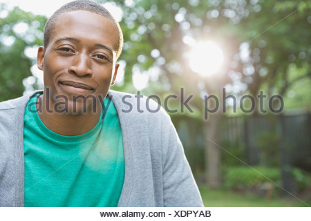 Portrait of smiling man in yard - Stock Photo