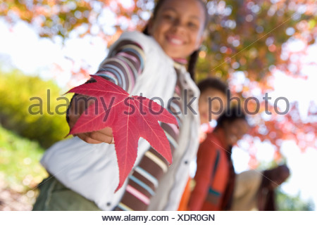 Family walking in autumn park focus on girl 7 9 holding red maple leaf smiling low angle view portrait tilt - Stock Photo
