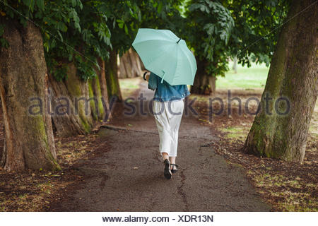 Rear view of young woman with umbrella strolling in park - Stock Photo