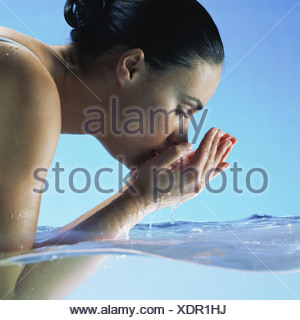 Woman in water cupping hands to face - Stock Photo