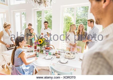 Family chatting around party table  in dining room - Stock Photo