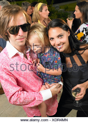 Couple with baby at a cocktail party - Stock Photo
