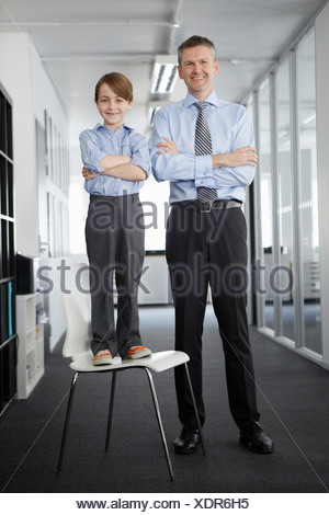 Father and son in office, boy standing on chair - Stock Photo