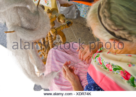 Woman spinning wool on a spinning wheel - Stock Photo