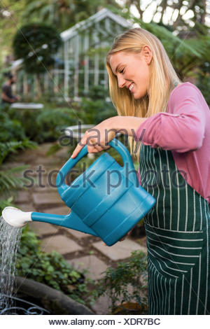 Side view of happy gardener watering plants against greenhouse - Stock Photo