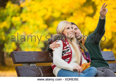 Young man showing something to woman while gesturing in park during autumn - Stock Photo