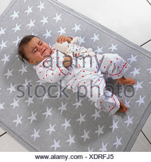Baby girl (7 months) lying on blanket holding a soft toy - Stock Photo