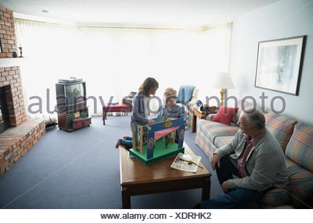 Grandfather watching grandchildren playing with old puppet set - Stock Photo