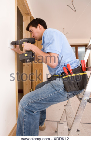 Electrician drilling outlet in wall - Stock Photo