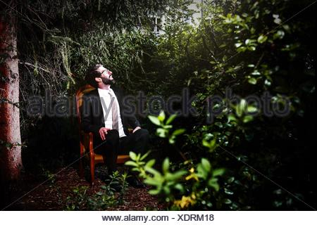 Man Wearing Suit Sitting On Chair In Yard While Looking Up - Stock Photo