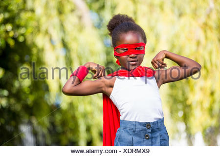 Cute mixed-race girl wearing a fancy dress and showing her biceps - Stock Photo