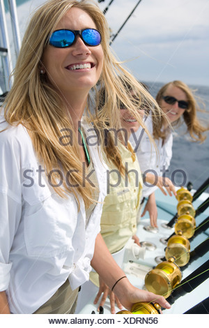 Blonde women deep sea fishing with their hands on the gold reels. - Stock Photo