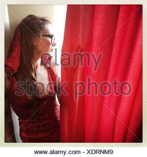 Young Woman Looking Behind Red Curtain - Stock Photo