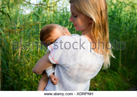 Rear view of mid adult mother and sleeping baby daughter in garden - Stock Photo