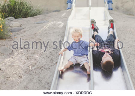 Two boys playing on  a slide at playground - Stock Photo