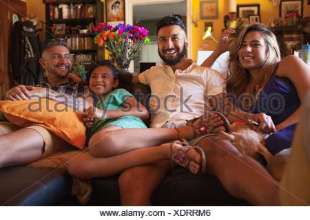 Girl and family watching TV on living room sofa - Stock Photo