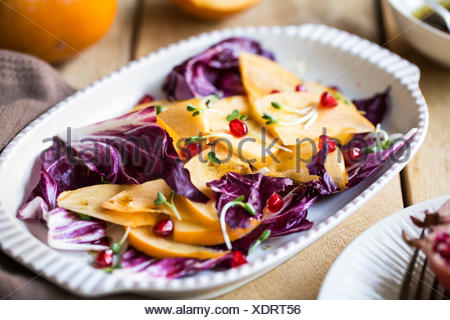 Persimmon with Radicchio and Pomegranate salad - Stock Photo