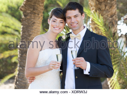 A bride and groom drinking champagne in their wedding clothes - Stock Photo
