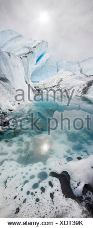Sun reflected in a pool of glacier water with ice fins on the Matanuska Glacier, Alaska - Stock Photo