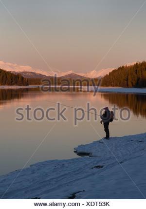 Lone fisherman fishing the Kenai River in Winter at Sunset - Stock Photo