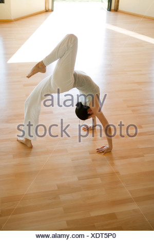 Woman doing one-legged wheel pose - Stock Photo