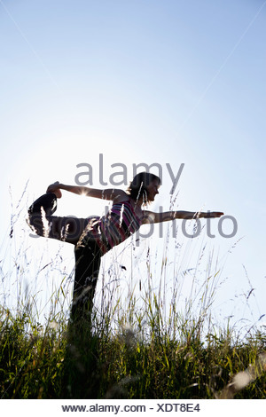 Woman Performing Yoga In Meadow - Stock Photo