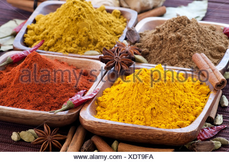 Exotically colorful spice mix with different podwer and grain in teak bowl as closeup - Stock Photo
