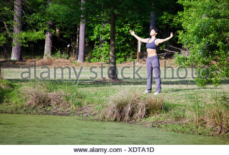 A woman stretching beside a lake, eyes closed - Stock Photo