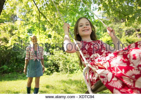 Summer. A girl in a sundress on a swing under a leafy tree. A woman standing behind her. - Stock Photo