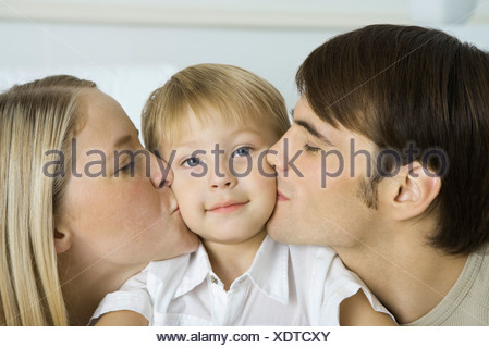 Parents kissing little boy's cheeks, boy smiling at camera - Stock Photo