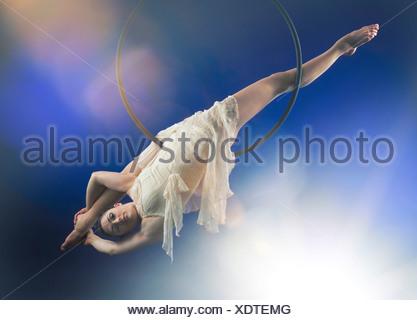 Studio shot of aerialist performing on hoop - Stock Photo