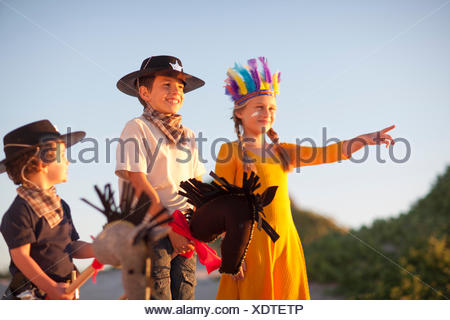 Three children dressed as native american and cowboys pointing from sand dunes - Stock Photo
