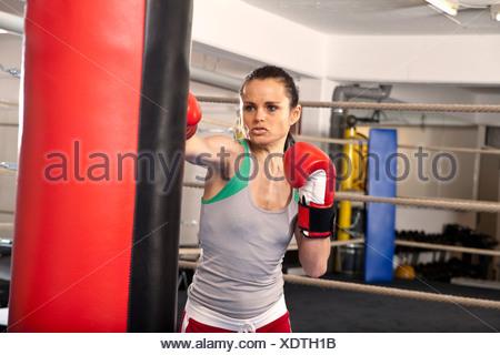 Young woman hitting punching bag - Stock Photo