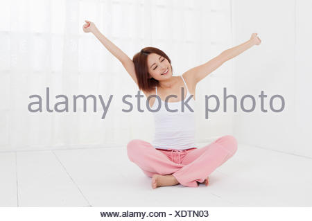 Young woman sitting on the floor with arms outstretched, - Stock Photo